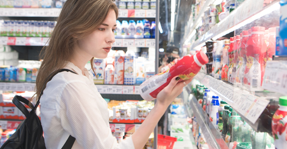 woman looking at product label at a grocery