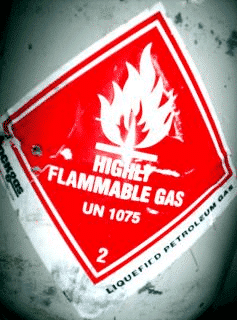 A FIRE HAZARD sign on a flammable gas container