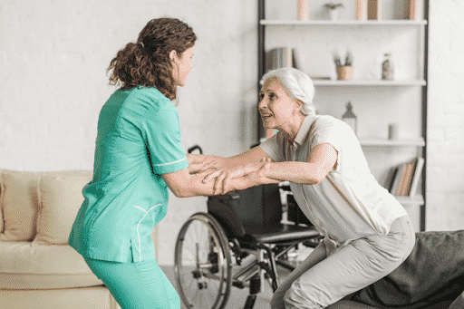 A nurse helping an aged patient stand up