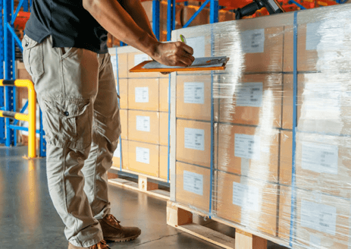 A worker checking on stretch-wrapped pallets inside a warehouse