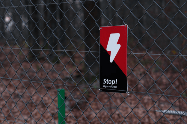 An ELECTRICAL HAZARD sign on a security fence