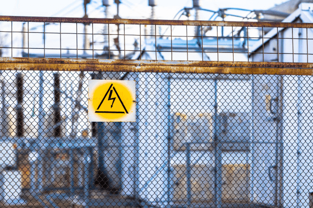 An electrical hazard sign hanging on a fence