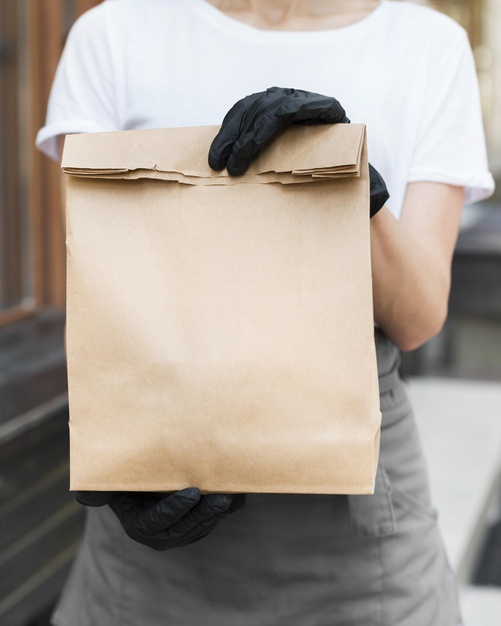 A person holding a bag of items with gloved hands