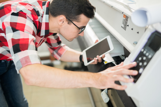 A retail store worker using his wireless device on a nearby printer