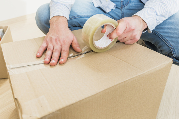 A box being sealed with pressure-activated plastic tape