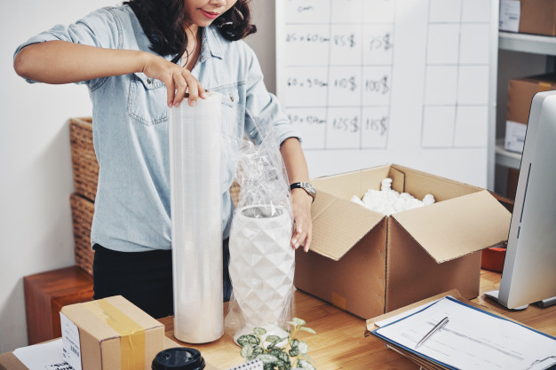 A woman packing a vase for shipment