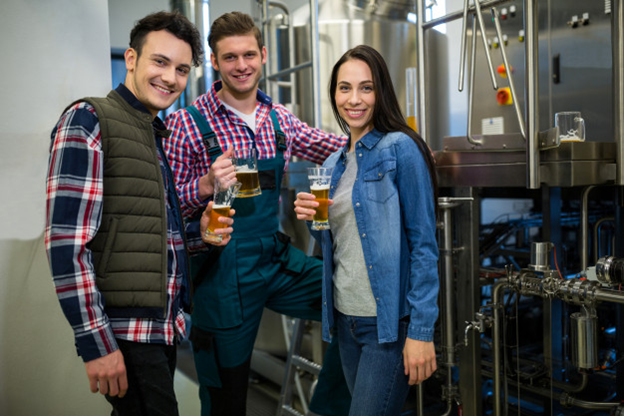 Friends drinking beer inside a brewery