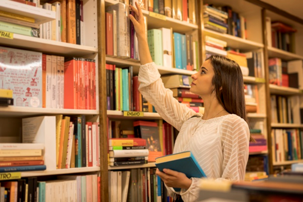 A young girl searching for books in the library