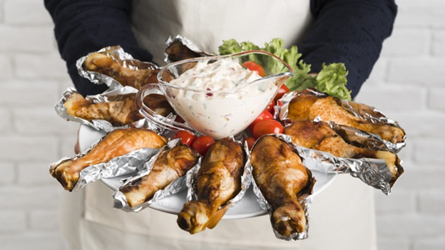 A chef holding a chicken platter