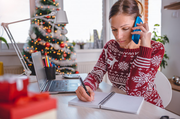 A woman working from a Christmas-embellished home office