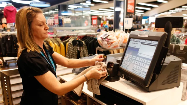 A sales clerk uses an omni-scanner at the checkout counter