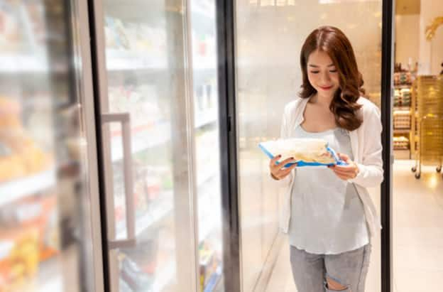 Woman-standing-in-front-of-freezer