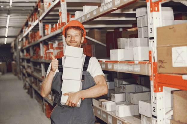An employee working inside a big warehouse