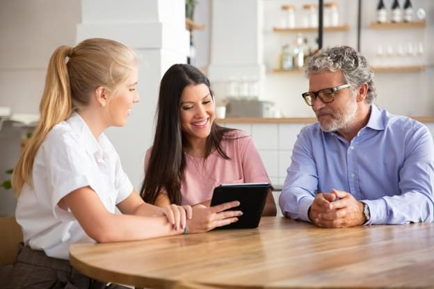 female-agent-manager-meeting-with-couple-young-mature-customers-presenting-content-tablet