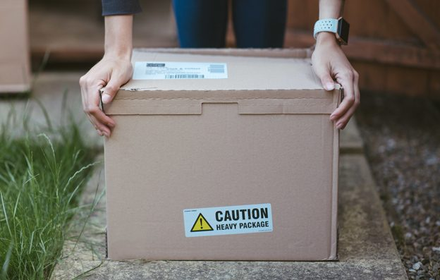person-resting-his-arms-cardboard-box-with-label-caution-heavy-package