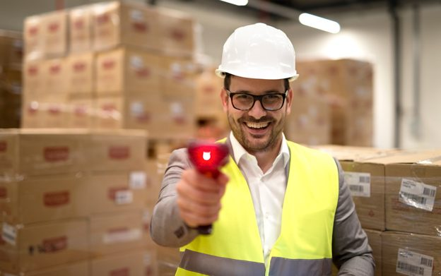 portrait-factory-warehouse-worker-standing-among-cardboard-boxes-holding-bar-code-scanner-laser-beam-pointing-camera